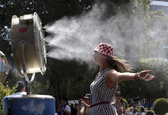 MUna joven sofoca el calor frente a un ventilador con nebulizador de agua durante la primera jornada del Abierto de Australia de tenis que se disputa en Melbourne (Australia), el 18 de enero de 2016 / David Crosling (EFE)
